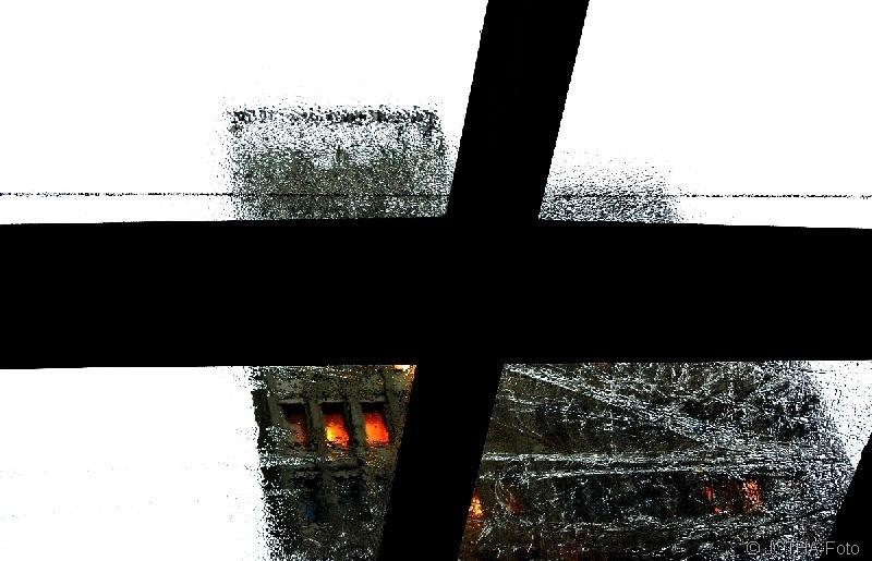 Blick durchs Dachfenster auf ein Hochhaus bei Regen
