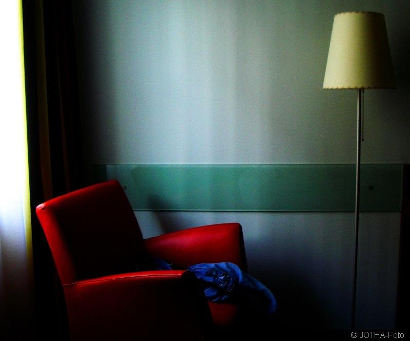 Blaue Hose auf rotem Sessel